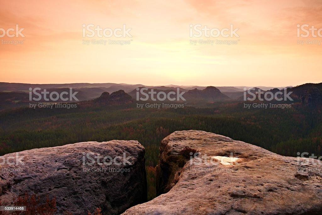 Sandstone cliff into forest valley, daybreak Sun at horizon. stock photo