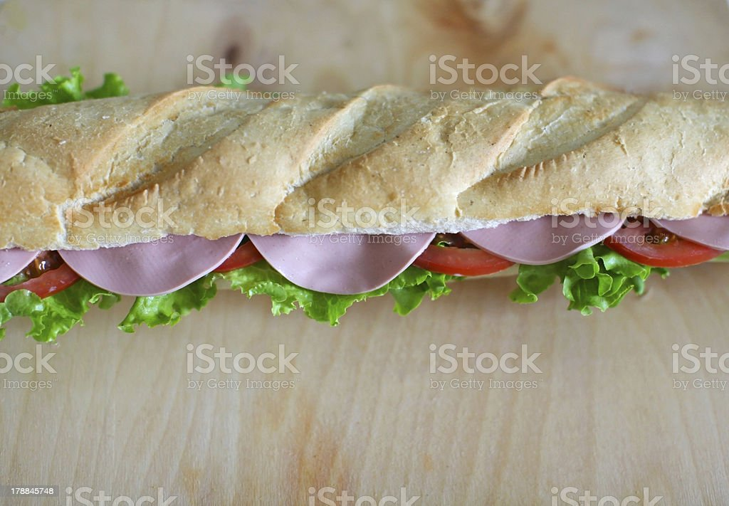 Sandwich baguette with chicken salami, salad and tomatoes royalty-free stock photo