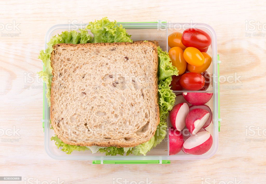Sandwich in a lunchbox with tomatoes and radish stock photo