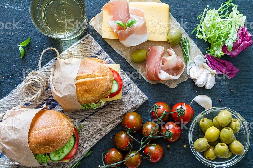 Sandwich ingredients - bread, ham, cheese, tomato, garlic, wine stock photo