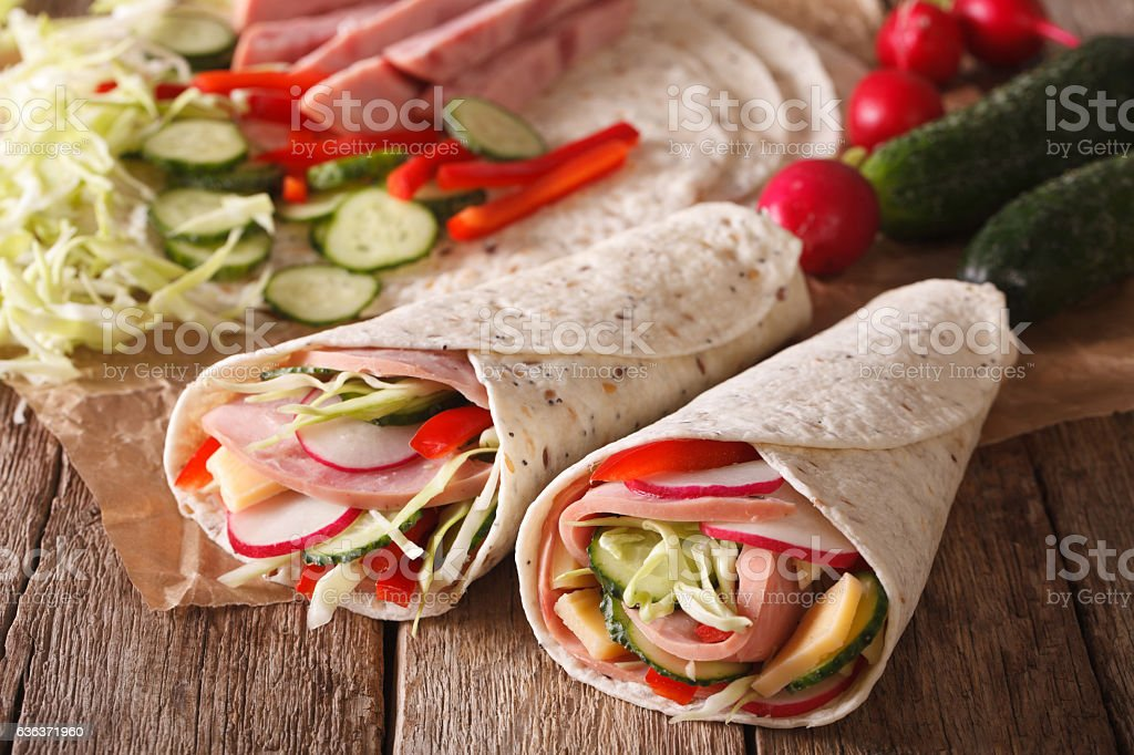 Sandwich roll filled with ham, cheese and fresh vegetables closeup stock photo