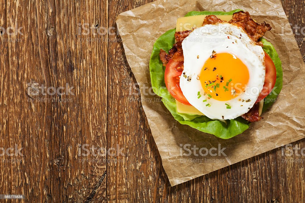 Sandwich with a fried egg, bacon, cheese and vegetables. stock photo