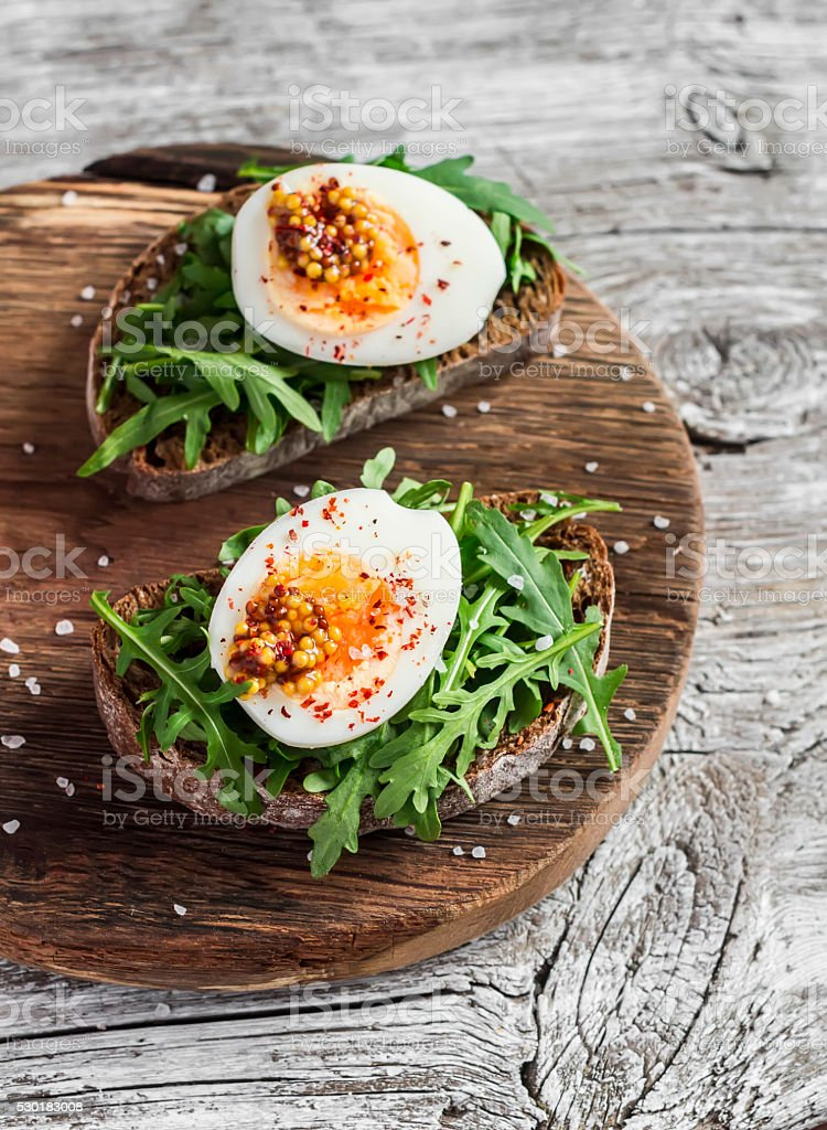 Sandwich with arugula, boiled egg and mustard stock photo