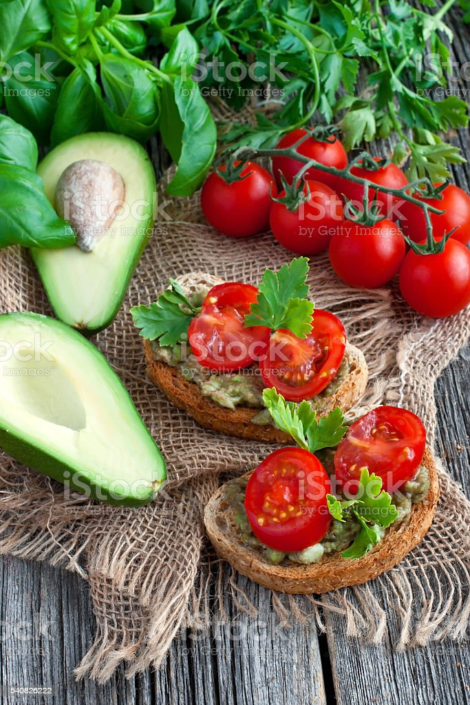 Sandwich with avocado and tomato on  wooden board stock photo