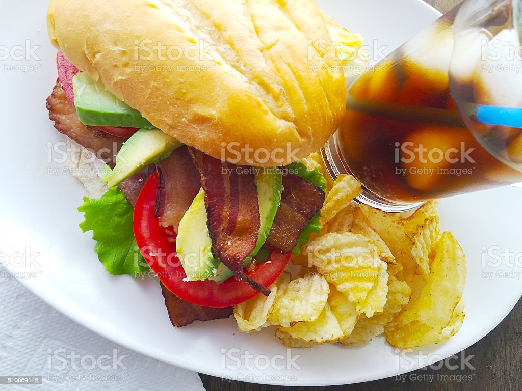 BLT sandwich with avocado, chips and soda stock photo