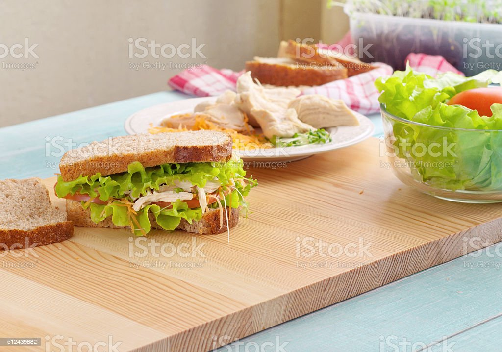 Sandwich with chicken on cutting board stock photo