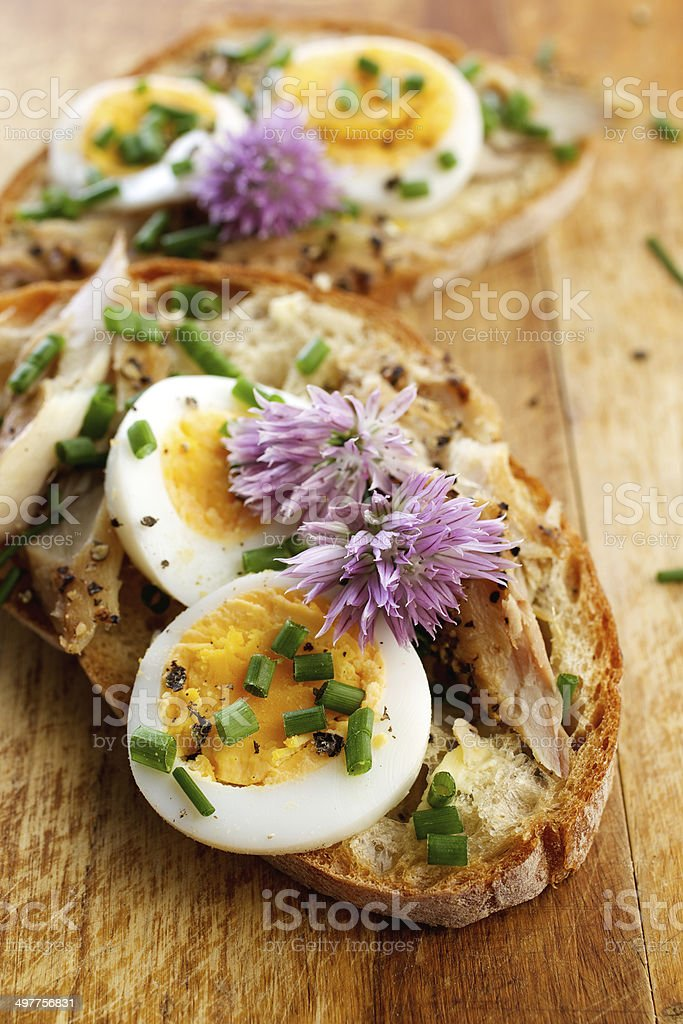 Sandwich with egg, mackerel and edible flowers of chives stock photo