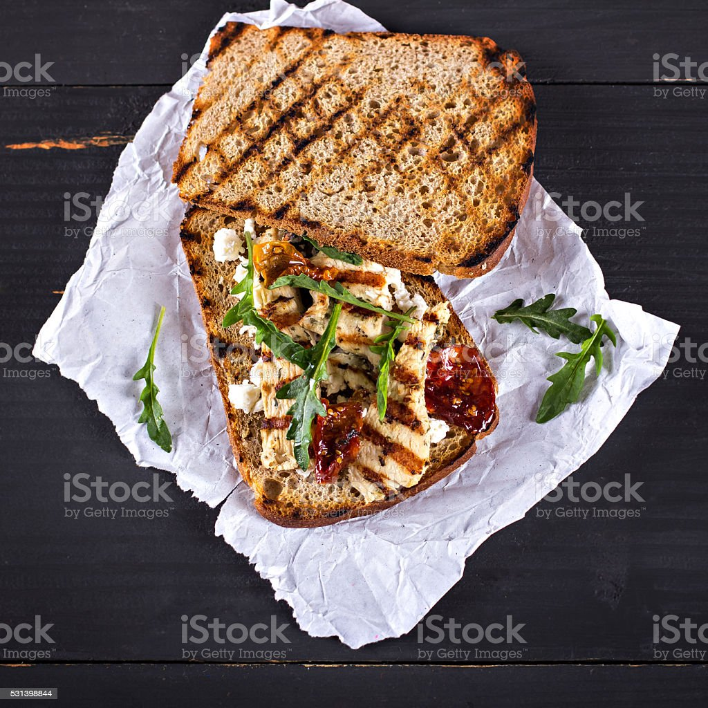 Sandwich with grilled chicken, sun-dried tomatoes, cheese and rocket salad stock photo