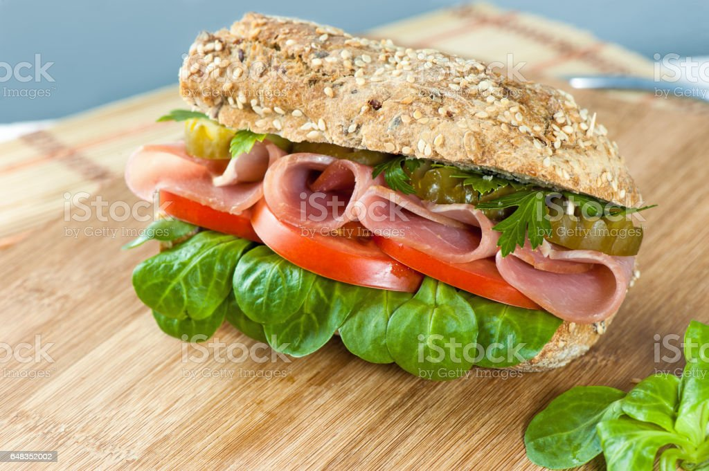 sandwich with ham, pickles, pepper, lettuce and tomato on the Board and napkin stock photo
