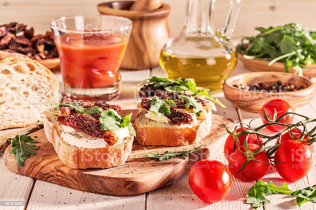 Sandwich with mozzarella, sun-dried tomatoes and arugula. stock photo