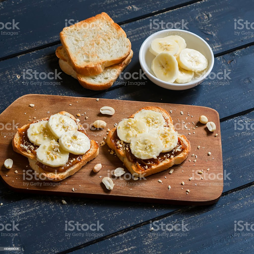 sandwich with peanut butter, banana and peanuts stock photo