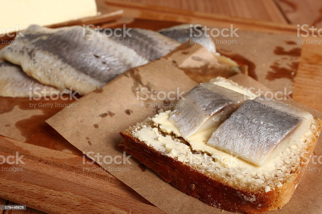 Sandwich with pickled herring and butter stock photo