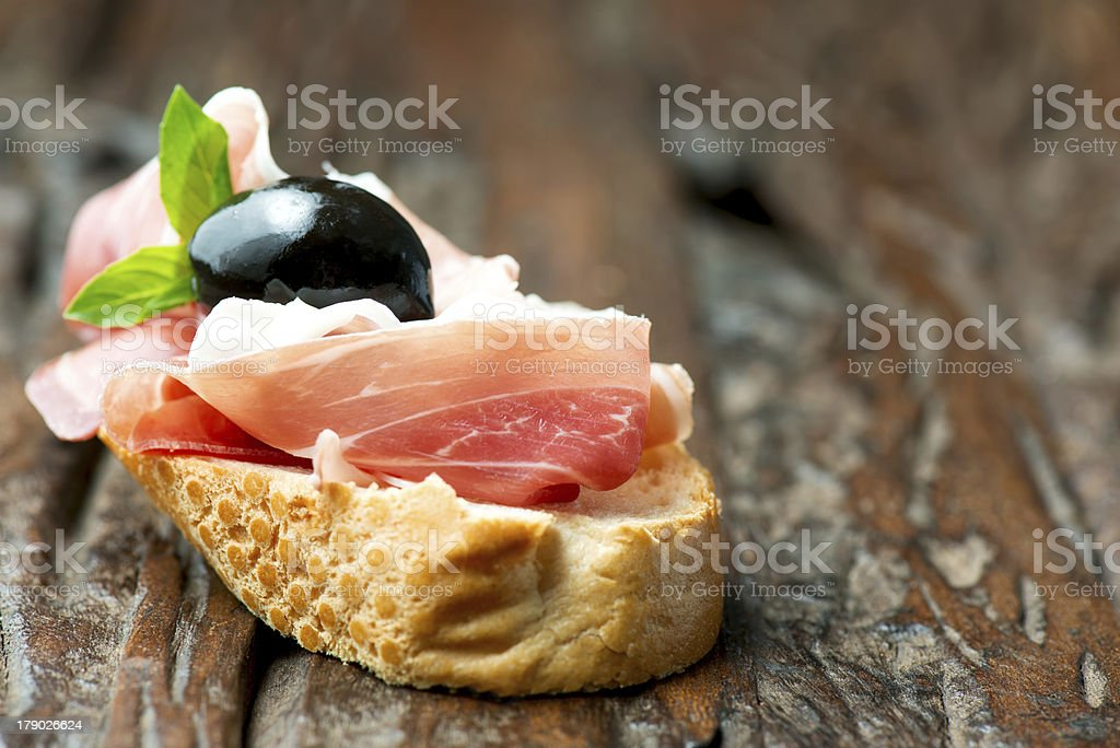 Sandwich with prosciutto olive on wooden old table horizontal royalty-free stock photo