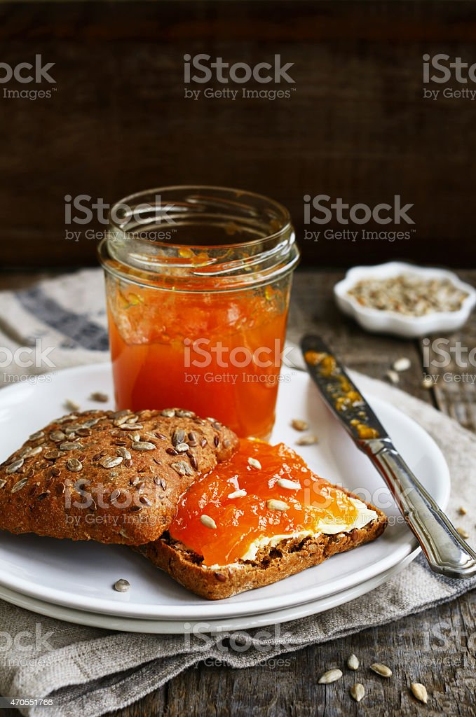 Sandwich with rye bread and apricot jam on dark background stock photo