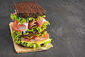 Sandwich with rye bread, ham, tomato, cheese and lettuce
