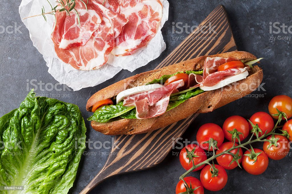 Sandwich with salad, prosciutto and mozzarella stock photo
