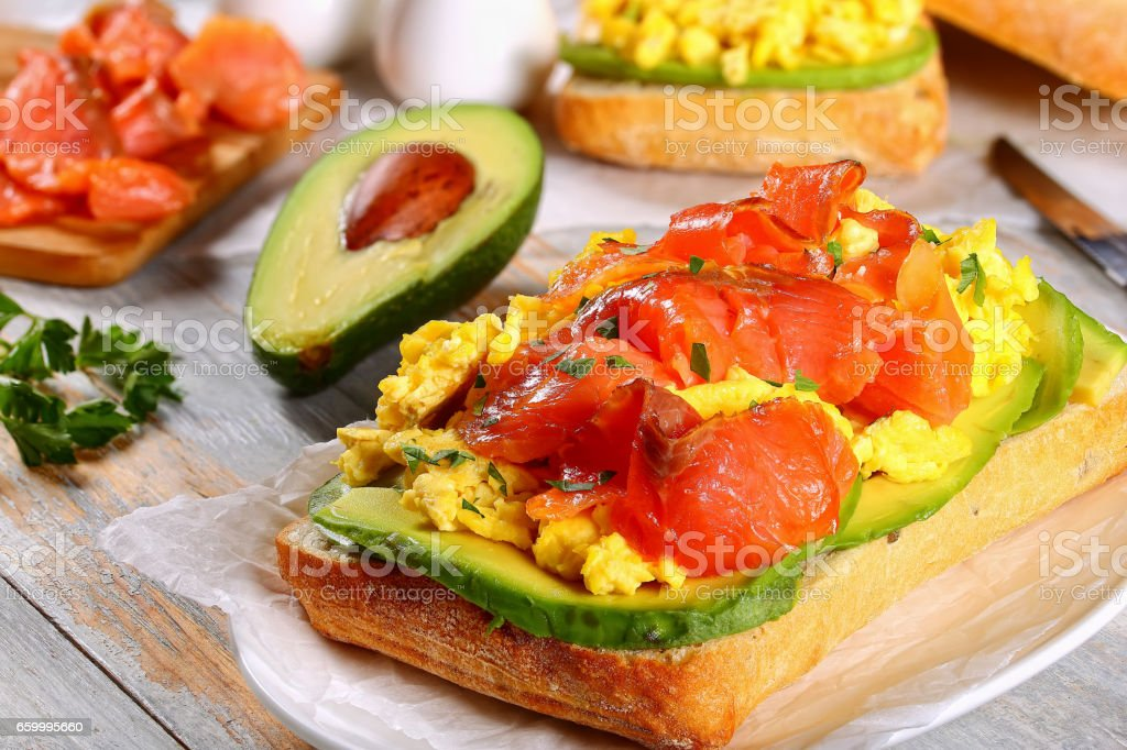 sandwich with salmon, avocado, scrambled eggs stock photo