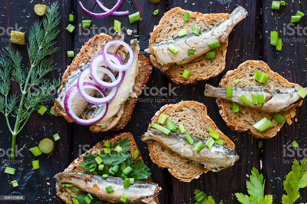 sandwich with sardines, sprinkle with onions on a black background stock photo