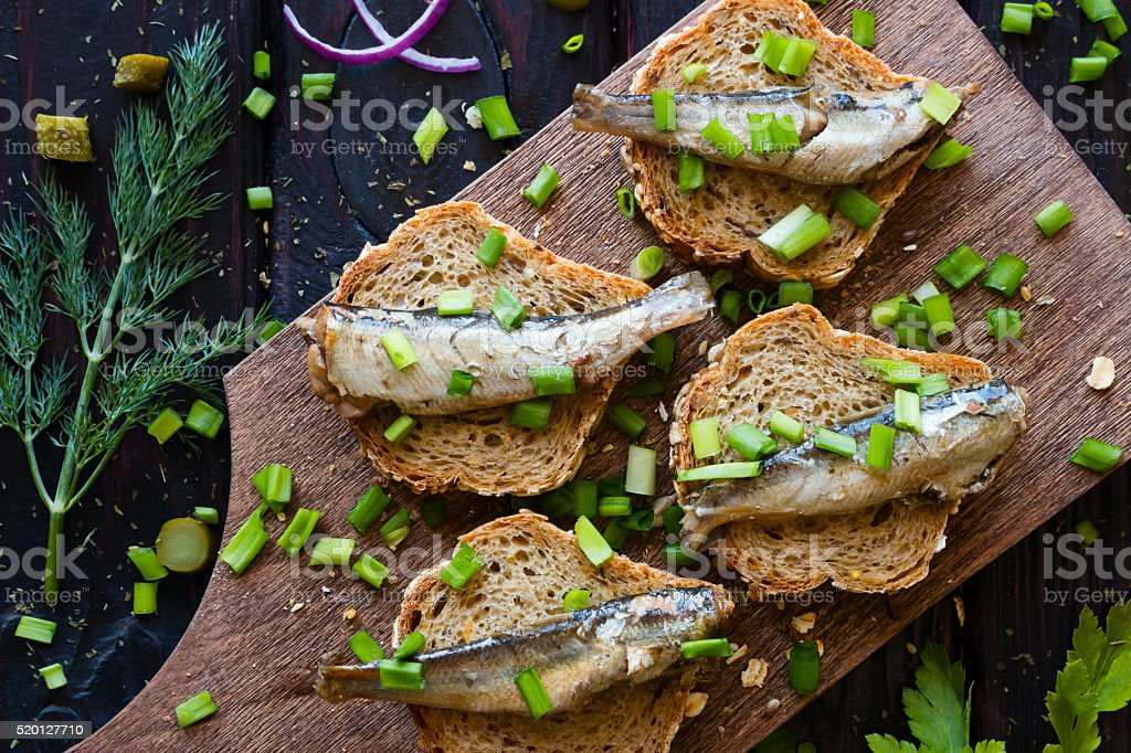 sandwich with sardines, sprinkle with onions on a cutting board stock photo