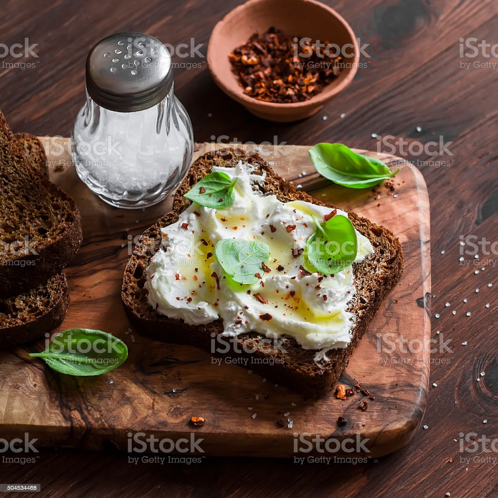 Sandwich with soft cheese, olive oil and basil stock photo