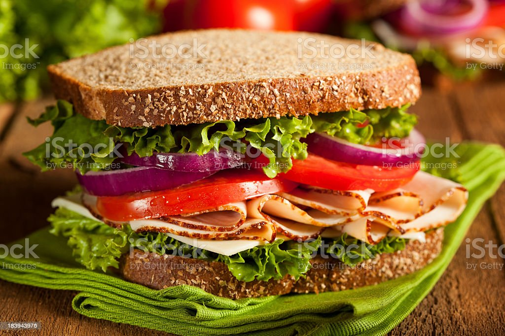 A sandwich with tomatoes, onions, and lettuce on wheat bread stock photo