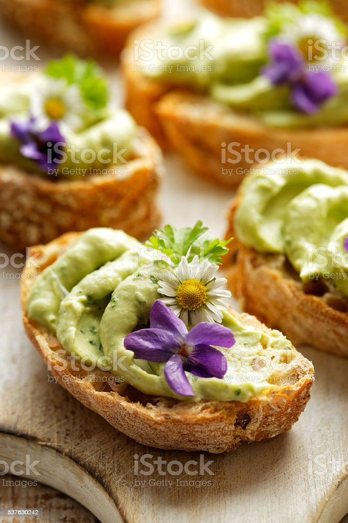 Sandwiches with avocado paste with the addition of edible flowers stock photo