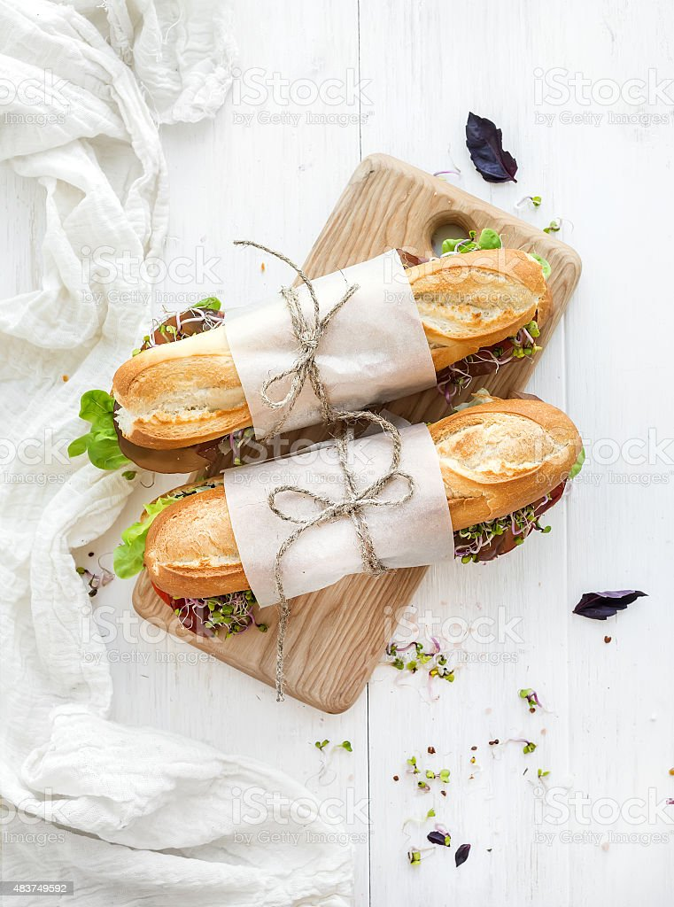 Sandwiches with beef, fresh vegetables and herbs on rustic wooden stock photo