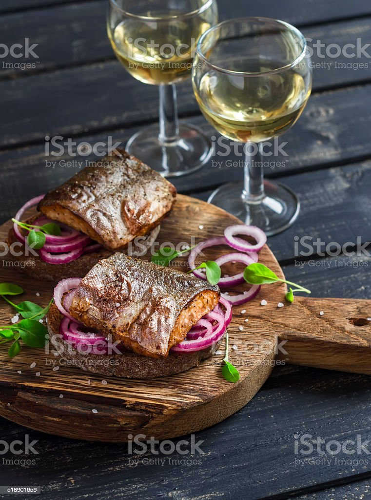 Sandwiches with grilled fish and quick pickled onions and white wine stock photo