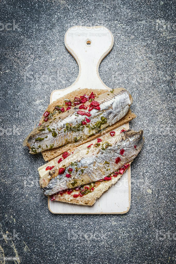 Sandwiches with herring on a white cutting board, top view stock photo