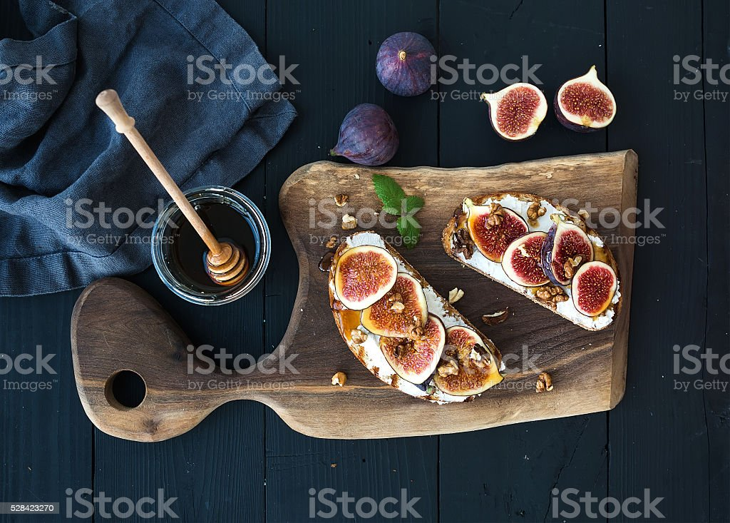 Sandwiches with ricotta, fresh figs, walnuts and honey on rustic stock photo