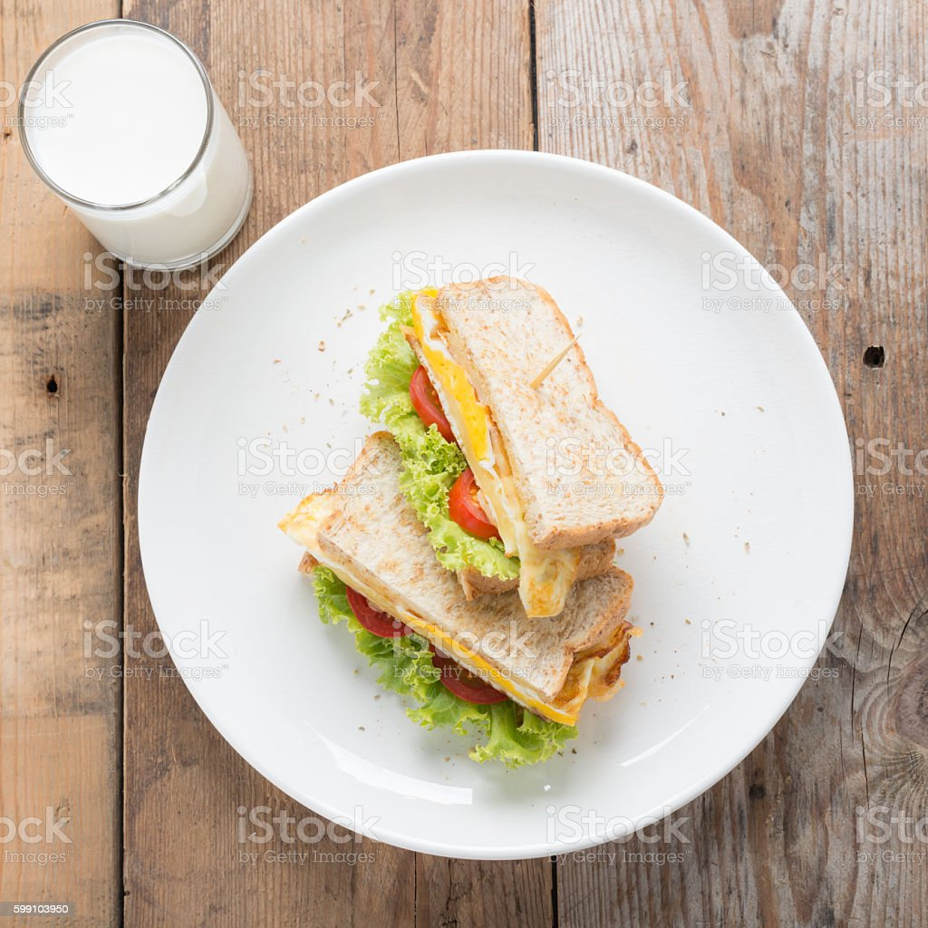 Sandwichs fried egg with cheese and milk on wood table. stock photo