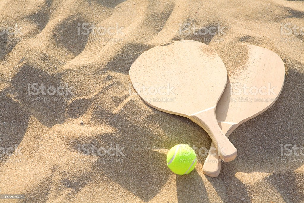 Sandy background with wonderfully contrasting beach racquet royalty-free stock photo