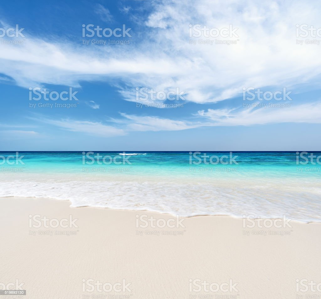 Sandy beach and cloudy sky background stock photo