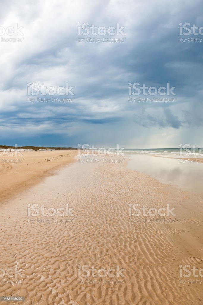 Sandy beach at the sea and storm clouds in the sky stock photo