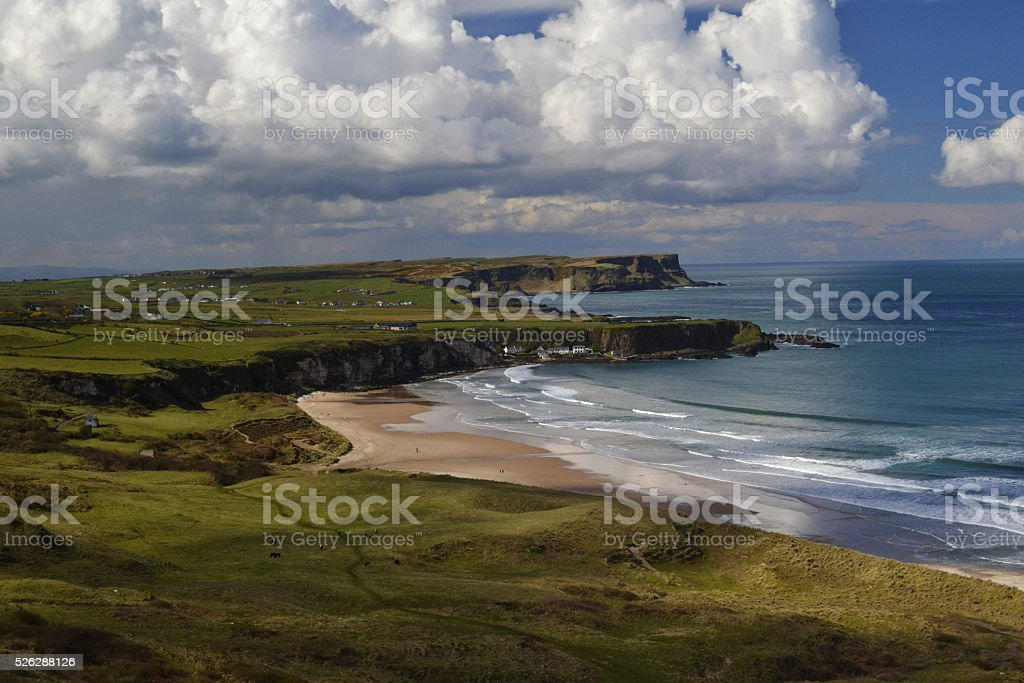 Sandy beach, blue ocean and green meadows and cliffs stock photo