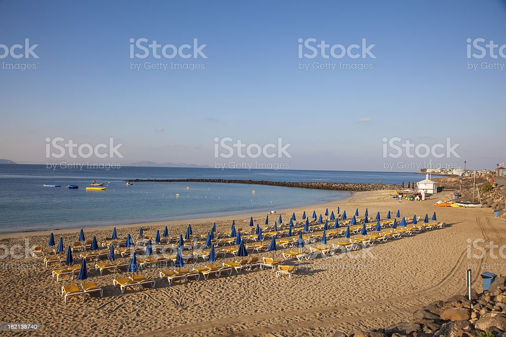 sandy beach in the morning with parasol royalty-free stock photo