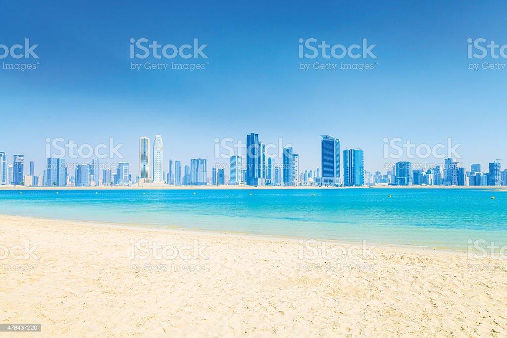 Sandy Beach, Sea and The City stock photo