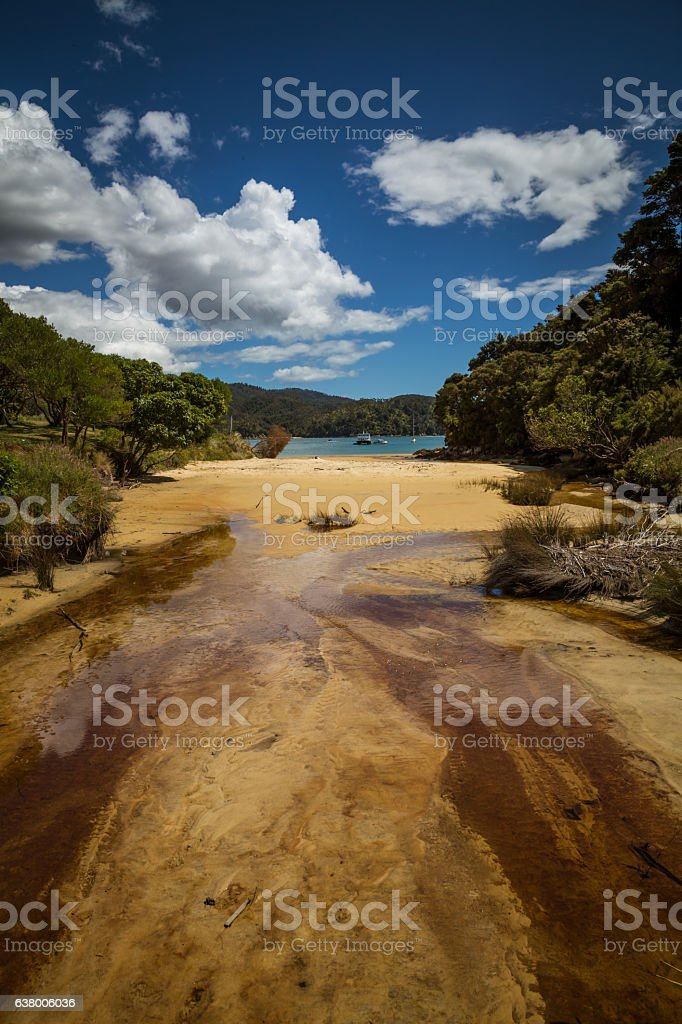Sandy beach under a blue sky with white clouds stock photo