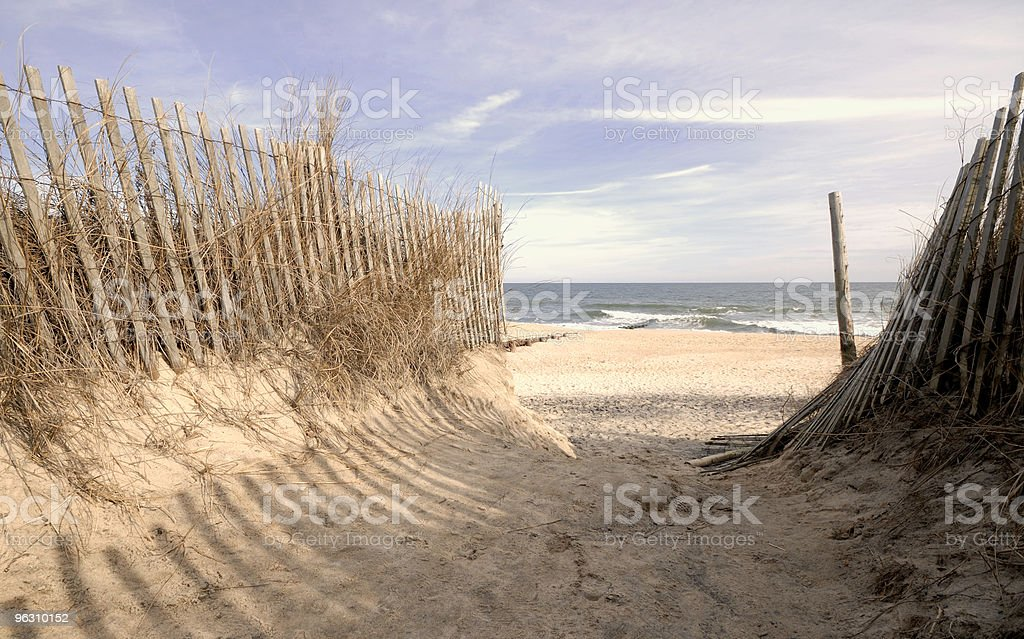 Sandy entrance to beach with waves hitting the shore. stock photo