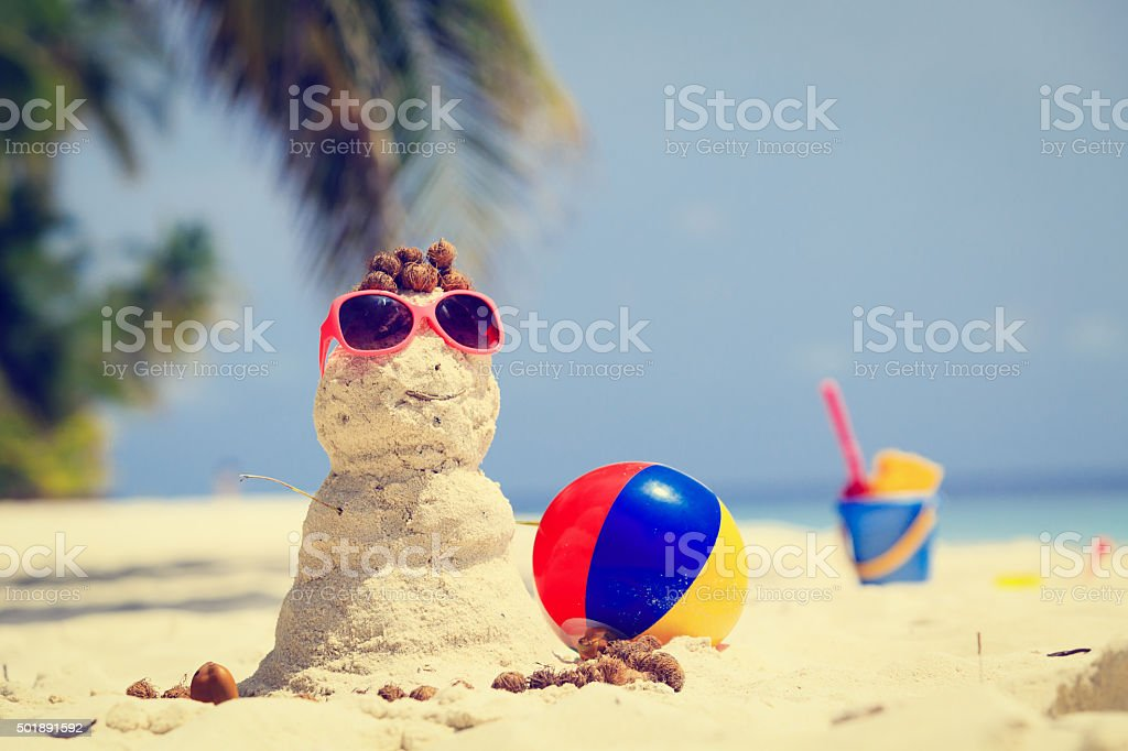 Sandy snowman and toys at tropical beach stock photo