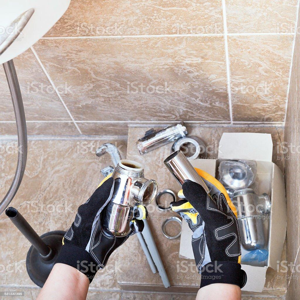 Sanitary technician repairs plumbing trap stock photo