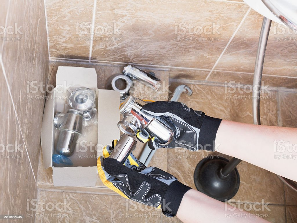 Sanitary technician replaces plumbing trap of sink stock photo