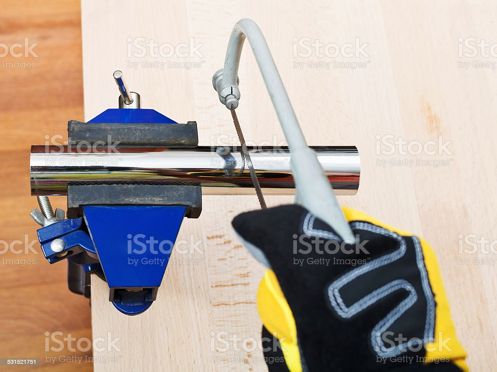 sanitary technician sawing plumbing drain pipe stock photo