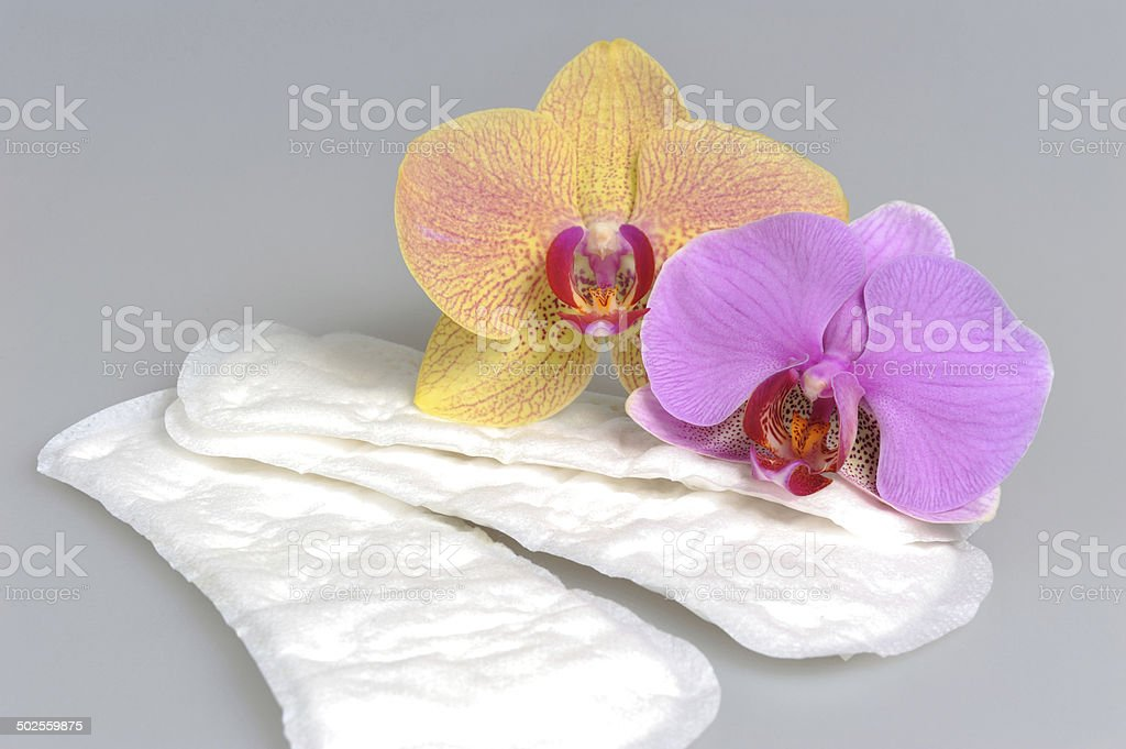Sanitary towels with orchid flowers on gray stock photo