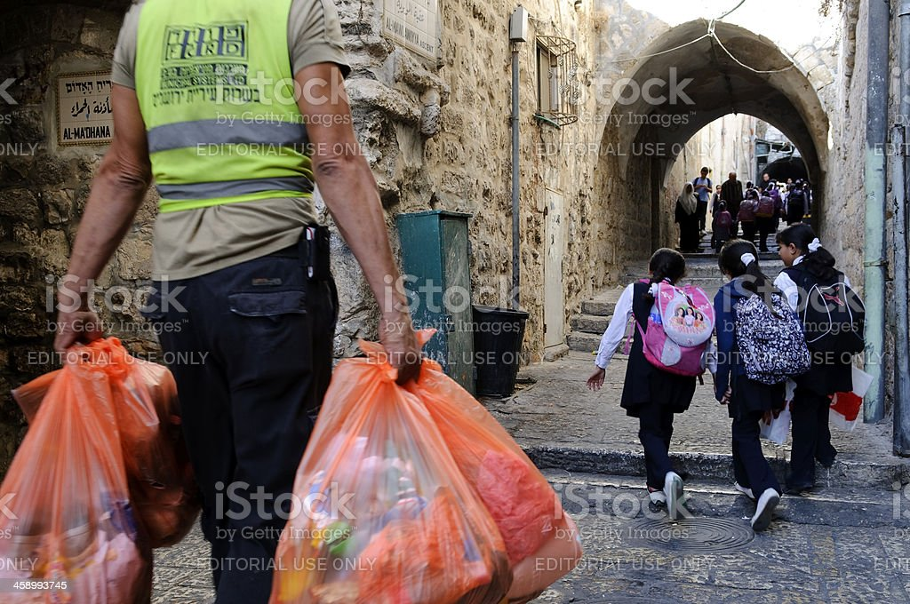 Garbage collection and school girls in Jerusalem's Muslim Quarter royalty-free stock photo