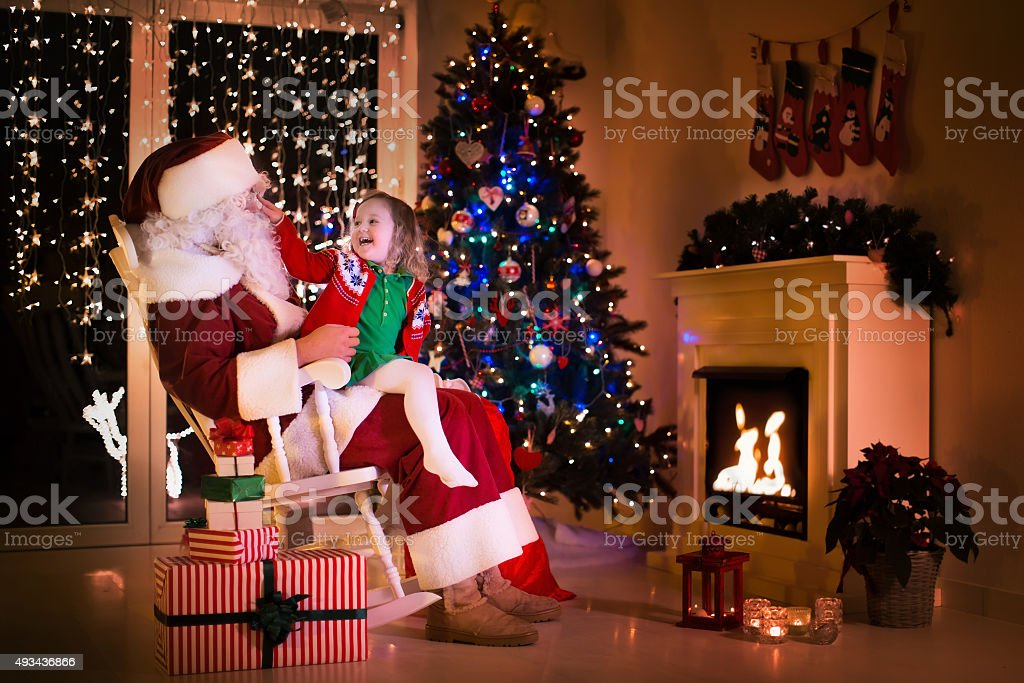 Santa and little girl under Christmas tree stock photo