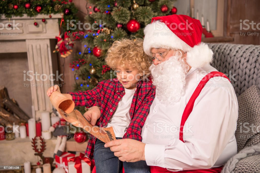 Santa Claus and child reading wishlist stock photo