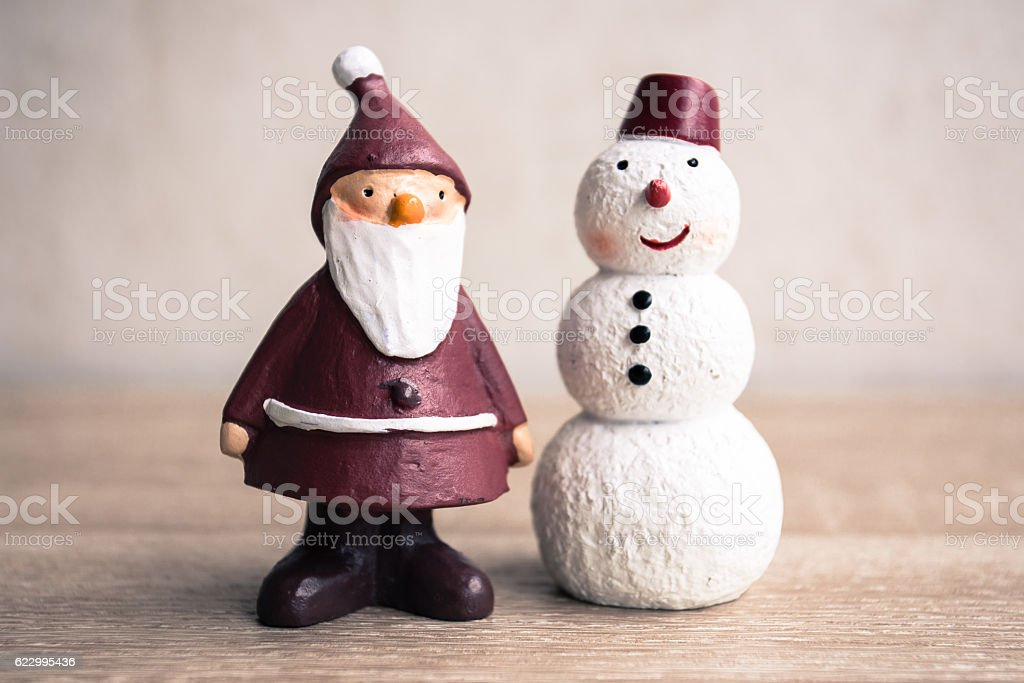 Santa claus and snowman with vintage filter, On wooden table. stock photo