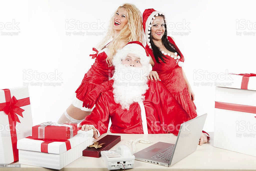 Santa Claus and two happy helpers in his office royalty-free stock photo