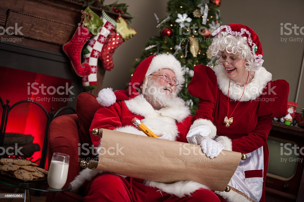 Santa Claus and Wife Working on Naughty and Nice List stock photo
